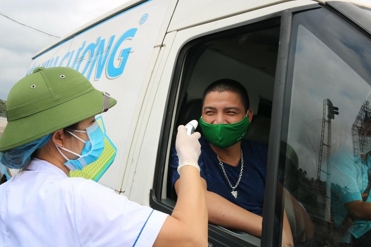 Nhân viên y tế tại chốt số 1 trên quốc lộ 5 kiểm tra y tế đối với lái xe, lái phụ và hành khách ra vào thành phố Hải Phòng . Ảnh: Giang Chinh