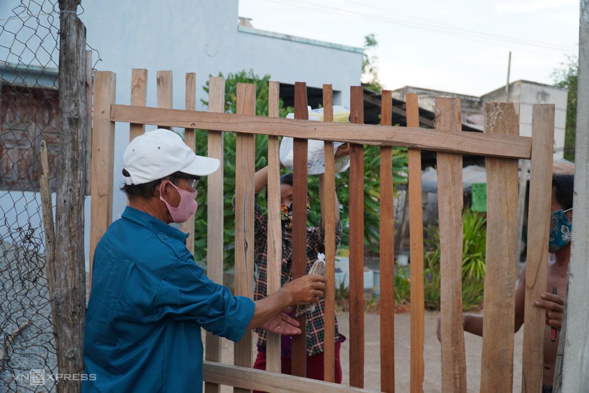 Dân quân tự vệ xã Phước Nam (Ninh Thuận) phát quà hỗ trợ của các mạnh thường quân cho một gia đường người Chăm trong vùng cách ly Văn Lâm 3. Ảnh: Việt Quốc