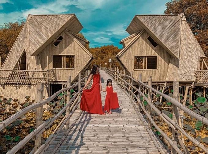 Hai mẹ con diện đồ đôi tạo dáng trên cầu tre. Ảnh Nguyễn Ngọc Hòa